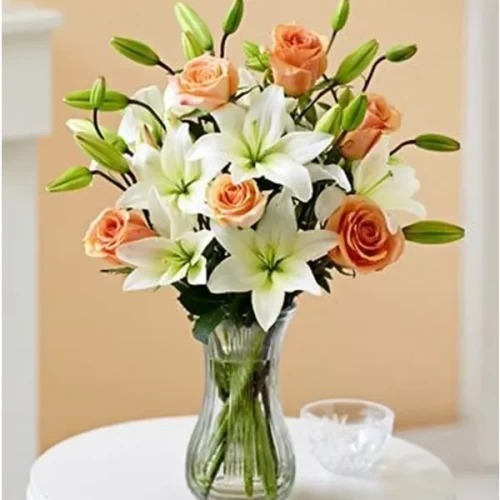 3 pcs white Lilly and 6 peach rose in a glass vase