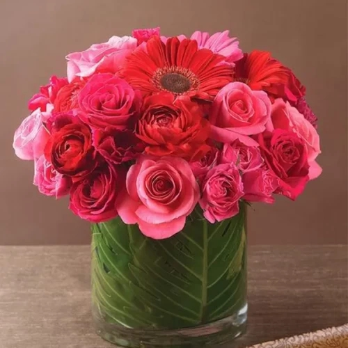 Arrangement of pink and red flowers in glass vase