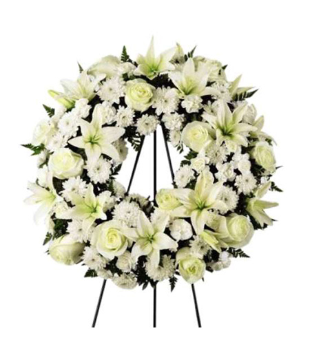 Round shaped lily and rose funeral arrangement