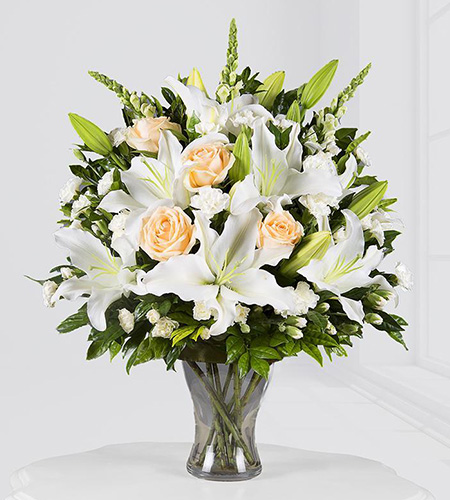 White lily and yellow rose glass vase arrangement