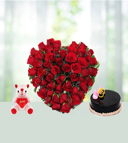 Appealing cake and teddy with heart shaped arrangement